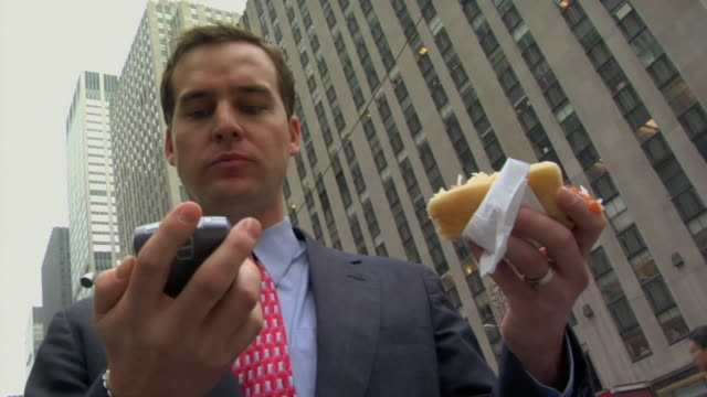 la cu businessman text messaging on his cell phone and eating sandwich on street / new york, new york, usa - radio city music hall stock videos & royalty-free footage