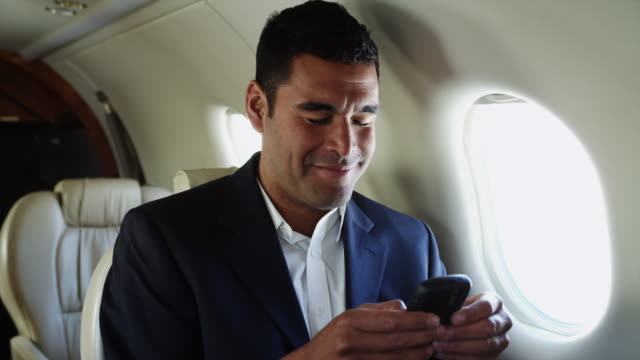 ms businessman texting in airplane / spanish fork, utah, usa - business travel stock videos & royalty-free footage