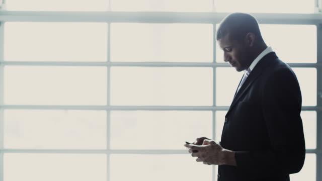 MS R/F Businessman texting in front of window, Squamish, British Columbia, Canada