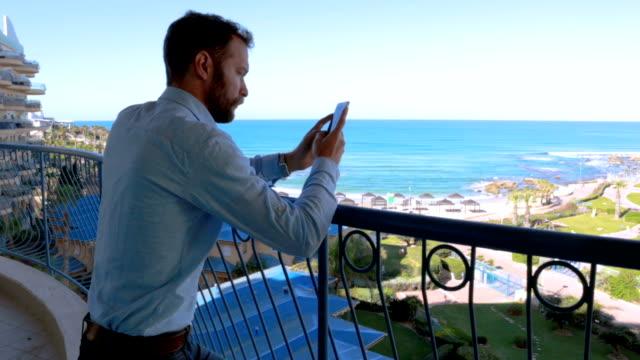 vidéos et rushes de textos d'homme d'affaires sur le balcon - vidéo de stock - barbe