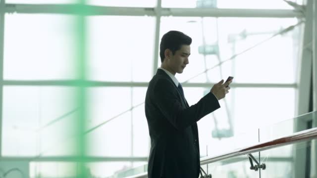 vídeos de stock e filmes b-roll de businessman texting on phone in modern office building. - vestuário de trabalho formal