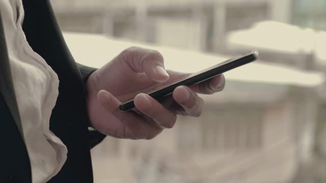 vídeos de stock, filmes e b-roll de empresário mensagem de texto em um smartphone - send