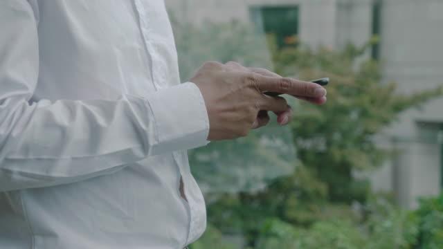 vídeos de stock e filmes b-roll de businessman texting on smartphone - antena equipamento de telecomunicações