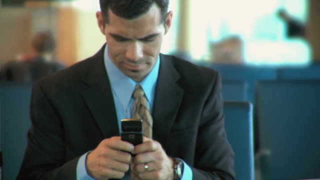 CU Businessman texting while waiting at airport terminal, Appleton, Wisconsin, USA