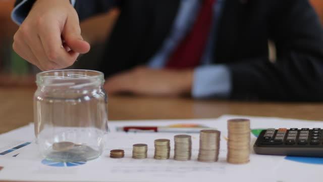 計画のためにガラス瓶にお金を投げるビジネスマン - コイントス点の映像素材/bロール