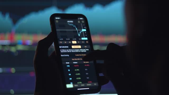 stockvideo's en b-roll-footage met zakenman die beurs op slimme telefoon voor het financiële scherm van de beurs handelt - spionage en toezicht