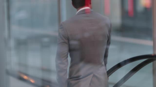 businessman travelling down escalator - escalator stock videos & royalty-free footage