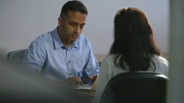 MS SELECTIVE FOCUS Businessman turns his laptop to face female colleague / Singapore