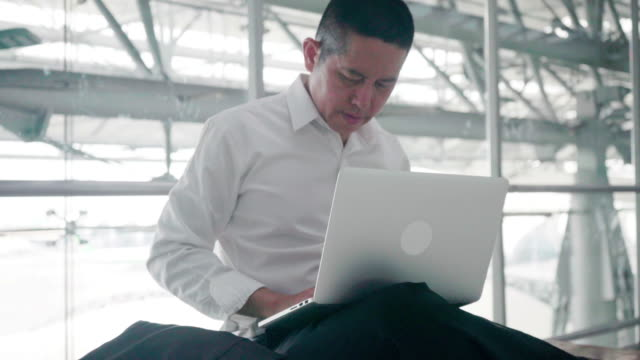 businessman typing e-mail sent to the customer to confirm the transaction between a waiting plane at the airport in thailand. - blogging stock videos & royalty-free footage