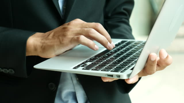businessman typing laptop and hold laptop on his hand - enter key stock videos & royalty-free footage