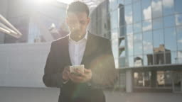 Businessman Typing Message on Mobile Phone