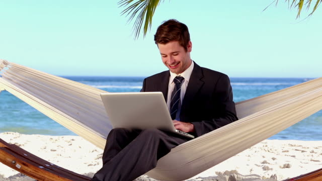 vidéos et rushes de businessman typing on his laptop in a hammock and smiling - costume complet