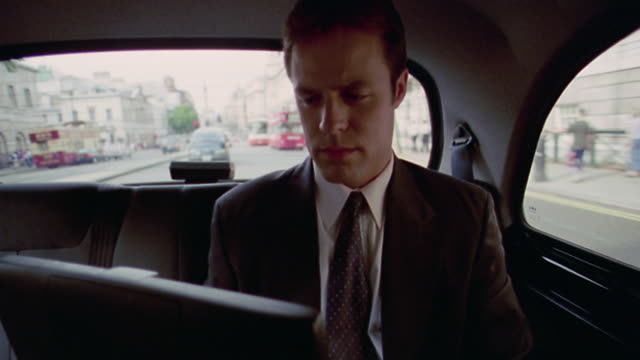 vidéos et rushes de businessman typing on laptop computer while riding in back of taxi / traffic in background / london, england - taxi