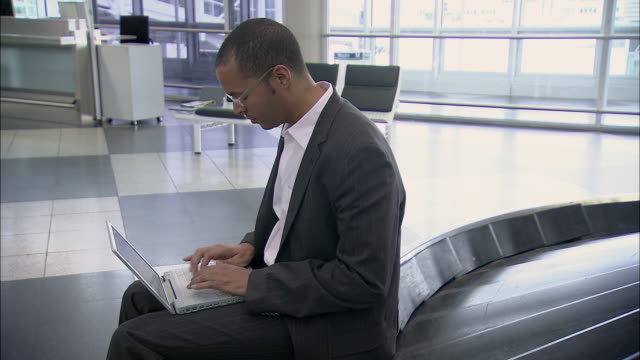 MS Businessman typing on laptop near empty airport baggage claim carousel / Munich, Germany