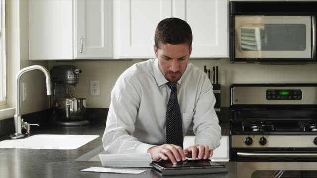 vídeos de stock, filmes e b-roll de ms businessman typing on tablet pc in kitchen / orem, utah, usa - orem