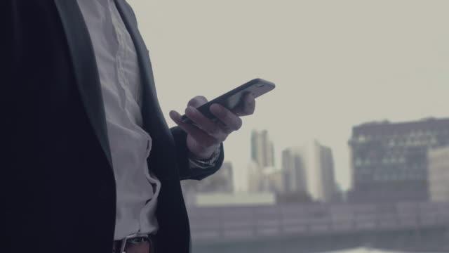 stockvideo's en b-roll-footage met zakenman te typen met behulp van smartphone smartphone - draagbaarheid