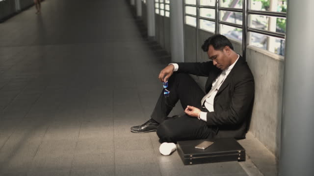 businessman unemployment he is sadness and sitting on sidewalk. - lost stock videos & royalty-free footage