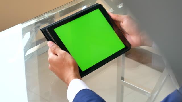 geschäftsmann verwendung green-screen-tablet auf glastisch: schulter-blick - halten stock-videos und b-roll-filmmaterial