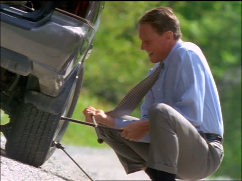 stockvideo's en b-roll-footage met businessman uses lug wrench to change tire / gets frustrated + kicks tire / sits on back of car - autoband