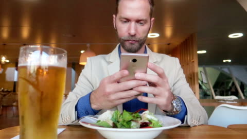 businessman uses smartphone at lunch - stock video - non alcoholic drink stock videos & royalty-free footage