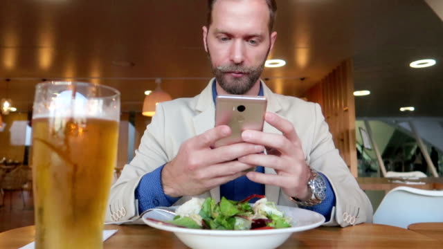 unternehmer nutzt smartphone beim mittagessen - stock video - alkoholfreies getränk stock-videos und b-roll-filmmaterial