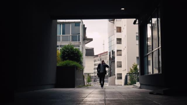 vidéos et rushes de slo mo homme d'affaires utilisant un smarthone et buvant un café tout en marchant dans la ville - un seul homme