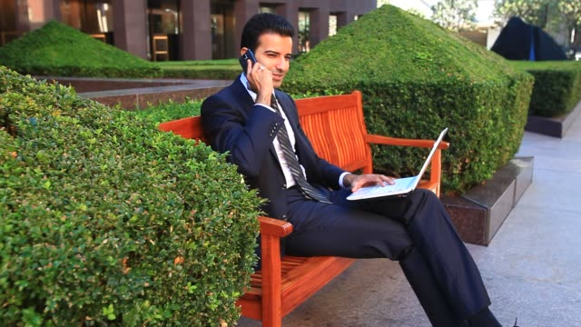 Businessman using a smartphone and laptop computer