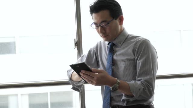 ビジネスマンはスマートフォンを使用して、ウィンドウ - スマートフォン点の映像素材/bロール