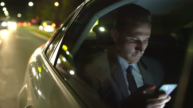 ms businessman using a smartphone in a taxi at night - business travel stock videos & royalty-free footage