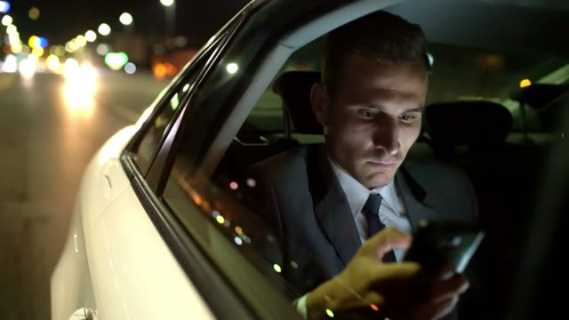 MS Businessman using a smartphone in the back seat of a limousine