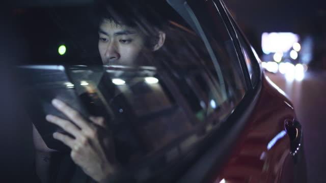 vidéos et rushes de l'homme d'affaires utilisant une tablette tout en conduisant retournent à la maison - taxi