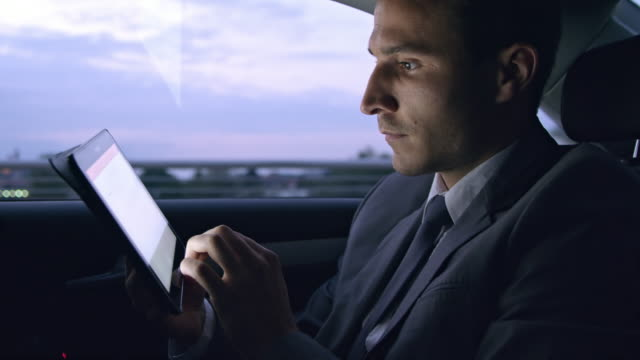 ms businessman using a tablet while sitting in the back seat of the car - busy morning stock videos & royalty-free footage