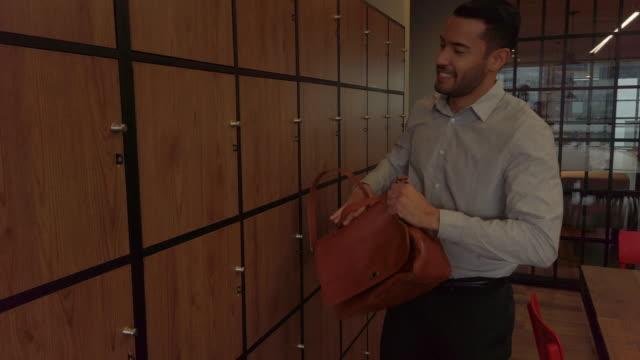 オフィスロッカーを使用するビジネスマン - ロッカー点の映像素材/bロール