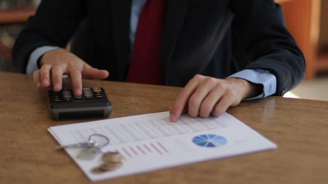 geschäftsmann mit taschenrechner - debt stock-videos und b-roll-filmmaterial