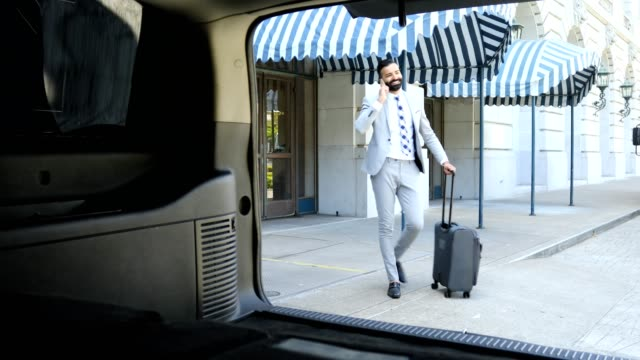 businessman using cell phone outside of hotel - wheeled luggage stock videos and b-roll footage