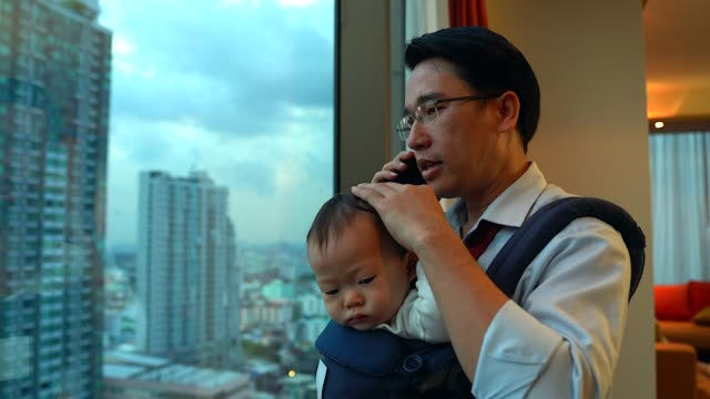 businessman using cellphone and laptop while carrying daughter at home - holding stock videos & royalty-free footage
