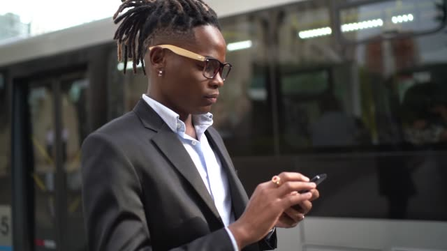 businessman using cellphone in the street - locs hairstyle stock videos & royalty-free footage