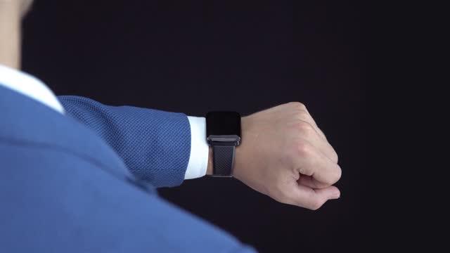vidéos et rushes de homme d'affaires utilisant la montre intelligente de cg - espace propre pour l'effet holographique. traqueurs de caméra sur le poignet - interface utilisateur graphique
