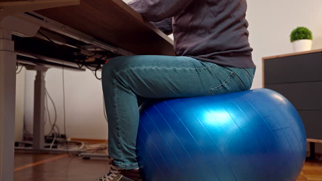 businessman using computer and headphones while sitting on exercise ball - fitness ball stock videos & royalty-free footage