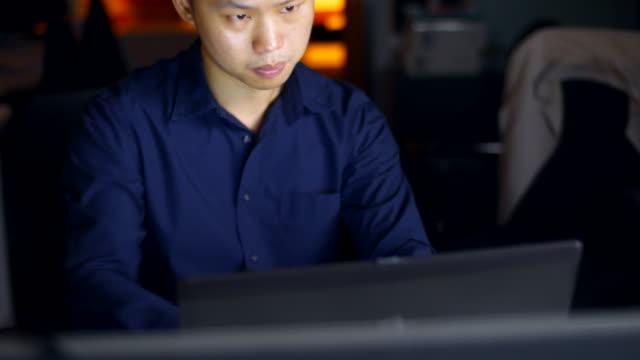 vídeos de stock e filmes b-roll de businessman using computer in office at night - camisa e gravata