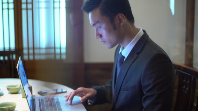 vidéos et rushes de ts businessman using computer in restaurant - seulement des jeunes hommes