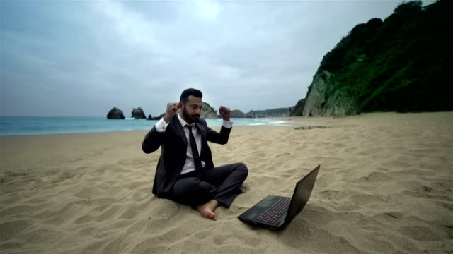businessman using computer on the beach - 4k resolution - freelance work stock videos & royalty-free footage