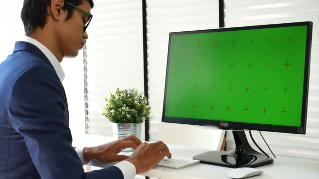 vídeos de stock e filmes b-roll de businessman using computer with green screen, chroma key - sobre os ombros vista traseira