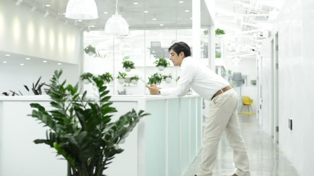 businessman using digital tablet at office corridor - もたれる点の映像素材/bロール