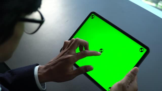 vídeos y material grabado en eventos de stock de empresario usando la pantalla verde de la tableta digital para los negocios - tecla de piano