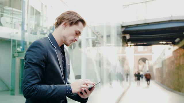 Homme d'affaires de DS à l'aide d'une tablette numérique devant un bâtiment