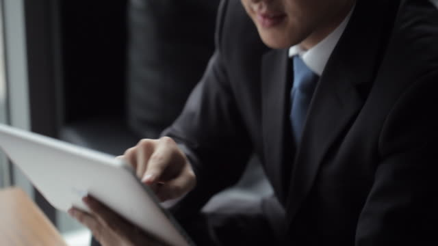 tu cu businessman using digital tablet in front of window / beijing, china - in front of stock videos & royalty-free footage
