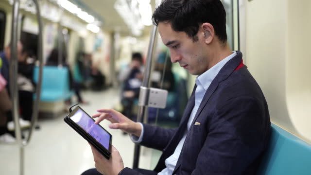 地下鉄の電車でデジタルタブレットを使用するビジネスマン - portability点の映像素材/bロール