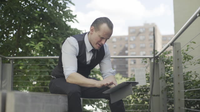 businessman using digital tablet outdoors - hochgekrempelte ärmel stock-videos und b-roll-filmmaterial