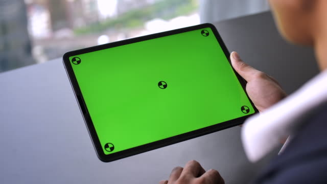 vídeos de stock e filmes b-roll de businessman using digital tablet with green screen, horizontal - sobre os ombros vista traseira